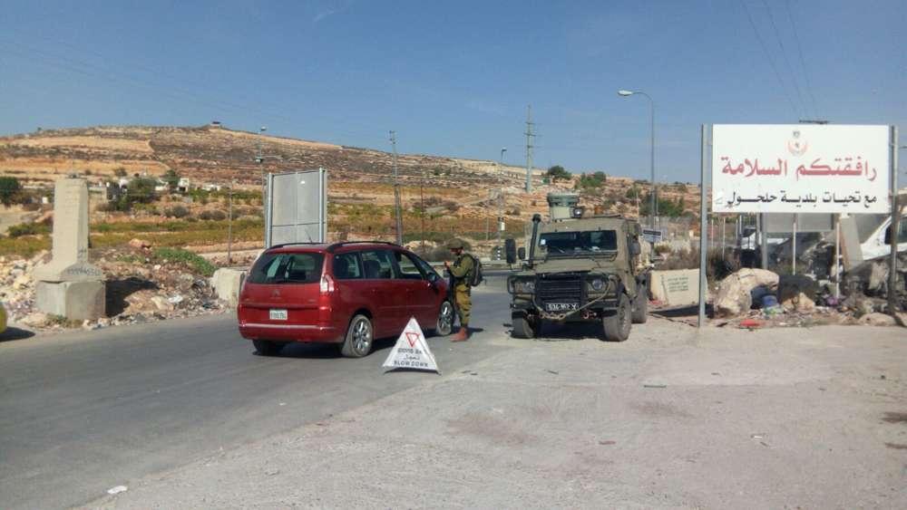 Soldados israelíes operan un puesto de control a la entrada de la aldea de Halhul, la ciudad natal de un terrorista musulmán que embistió con su automóvil a dos israelíes más temprano en el día, el 17 de noviembre de 2017. (Fuerzas de Defensa de Israel)