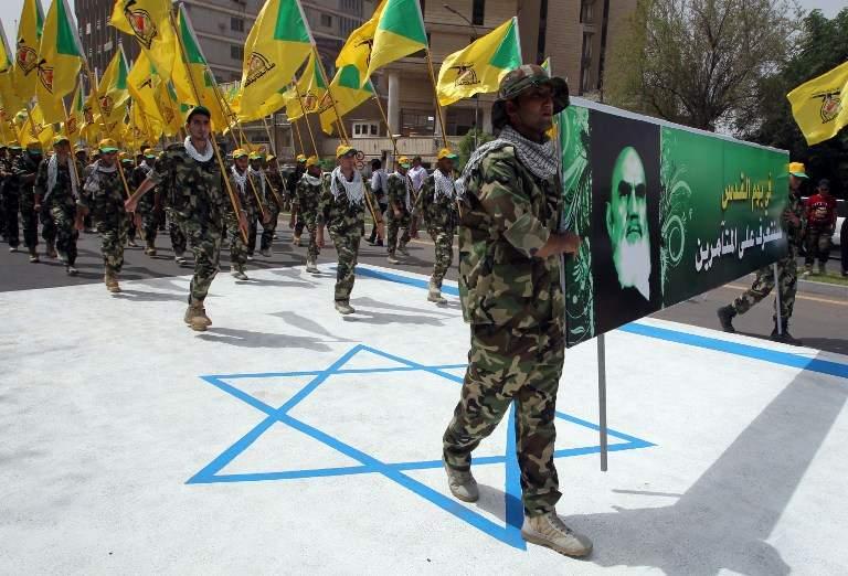 Ilustrativo: los miembros iraquíes de Hezbolá sostienen las banderas amarillas de la rama iraquí del grupo terrorista libanés y un retrato del último líder supremo de Irán, el ayatolá Ruhollah Khomeini, mientras caminan sobre una bandera israelí pintada en el suelo durante un desfile que marca el día Internacional Al-Quds el 25 de julio de 2014, en la capital iraquí, Bagdad. (AFP / Ali al-Saadi)