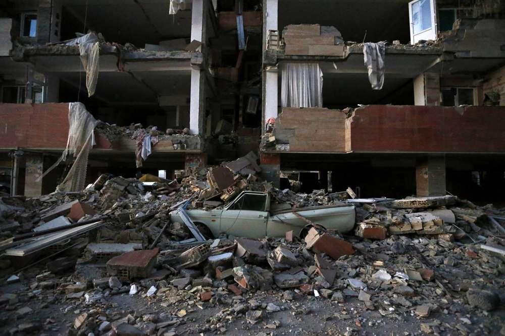 En esta foto provista por la Agencia de Noticias de los Estudiantes Iraníes, ISNA, un automóvil yace destrozado por escombros del terremoto en la ciudad de Sarpol-e-Zahab en el oeste de Irán, el lunes 13 de noviembre de 2017. (Pouria Pakizeh / ISNA via AP )