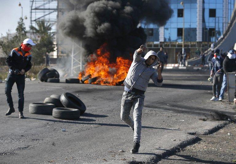 Árabes lanzan piedras hacia las tropas israelíes en un puesto de control israelí cerca de la ciudad de Ramallah el 8 de diciembre de 2017. (AFP / Abbas Momani)