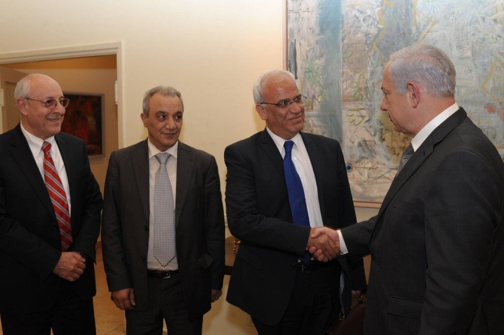 El primer ministro Benjamin Netanyahu le da la mano a Saeb Erekat en Jerusalém, abril de 2012. El ayudante de Netanyahu Yitzhak Molcho está a la izquierda y el jefe de seguridad de la Autoridad Palestina Majed Faraj está a la izquierda. (Amos Ben Gershom / GPO / Flash 90)
