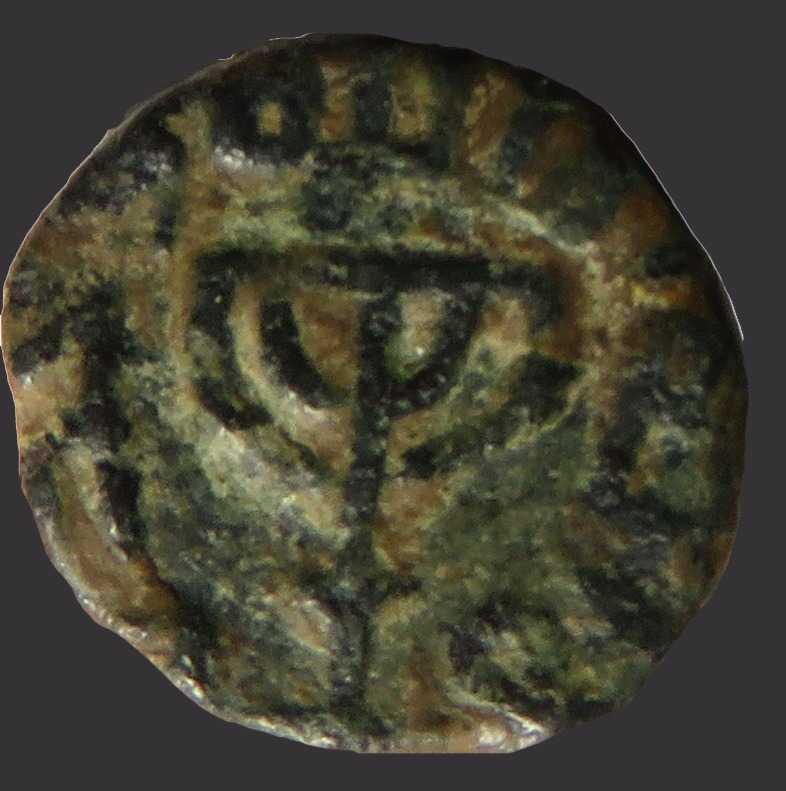 """En el centro de una moneda musulmana acuñada por Jerusalém del período omeya (siglo VIII) se encuentra una Menorah de cinco brazos. Por un lado, la inscripción en árabe """"No hay más dios que Alá"""". En el otro lado de la moneda está la inscripción árabe 'Muhammad, el mensajero de dios'. (cortesía de Assaf Avraham)"""