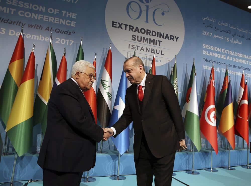 El presidente de Turquía, Recep Tayyip Erdogan, estrecha la mano del presidente de la Autoridad Palestina Mahmoud Abbas en la Cumbre Extraordinaria de la Organización de Cooperación Islámica en Estambul, miércoles 13 de diciembre de 2017. (Yasin Bulbul / Pool Photo via AP)
