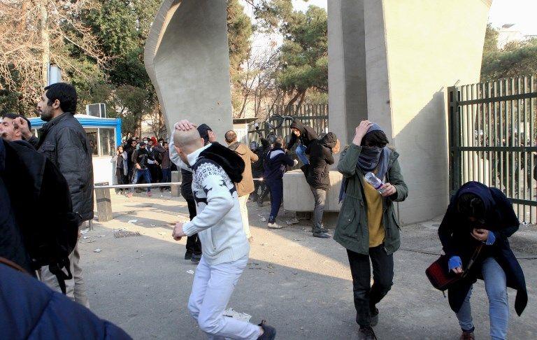 Estudiantes iraníes huyen del gas lacrimógeno en la Universidad de Teherán durante una manifestación el 30 de diciembre de 2017. (AFP PHOTO / STR)