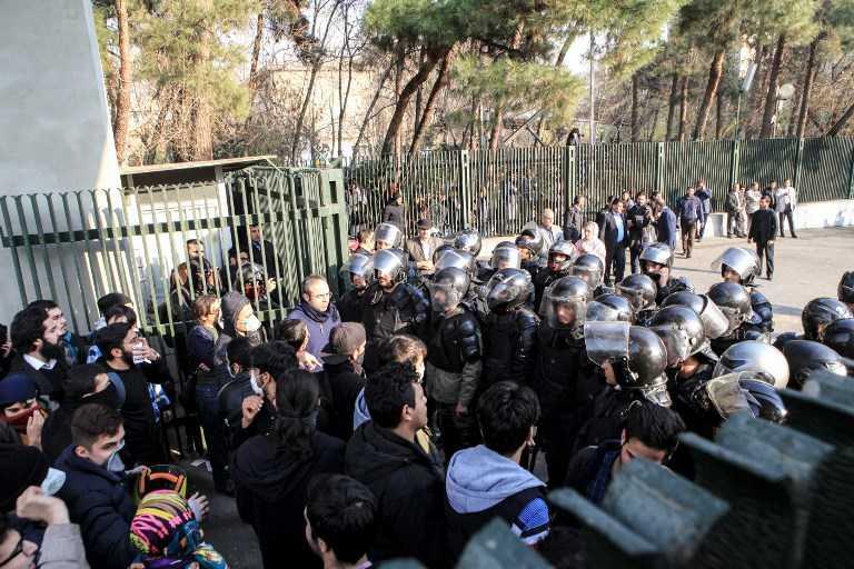 Estudiantes iraníes se enfrentan con la policía en la Universidad de Teherán durante una manifestación el 30 de diciembre de 2017. (AFP PHOTO / STR)