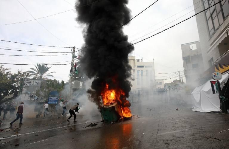 Fuerzas de seguridad libanesas disparan gases lacrimógenos para dispersar a los manifestantes mientras un incendio arde en un contenedor de basura durante una manifestación frente a la embajada de Estados Unidos en Awkar, en las afueras de la capital libanesa, Beirut, el 10 de diciembre de 2017. (AFP / ANWAR AMRO)