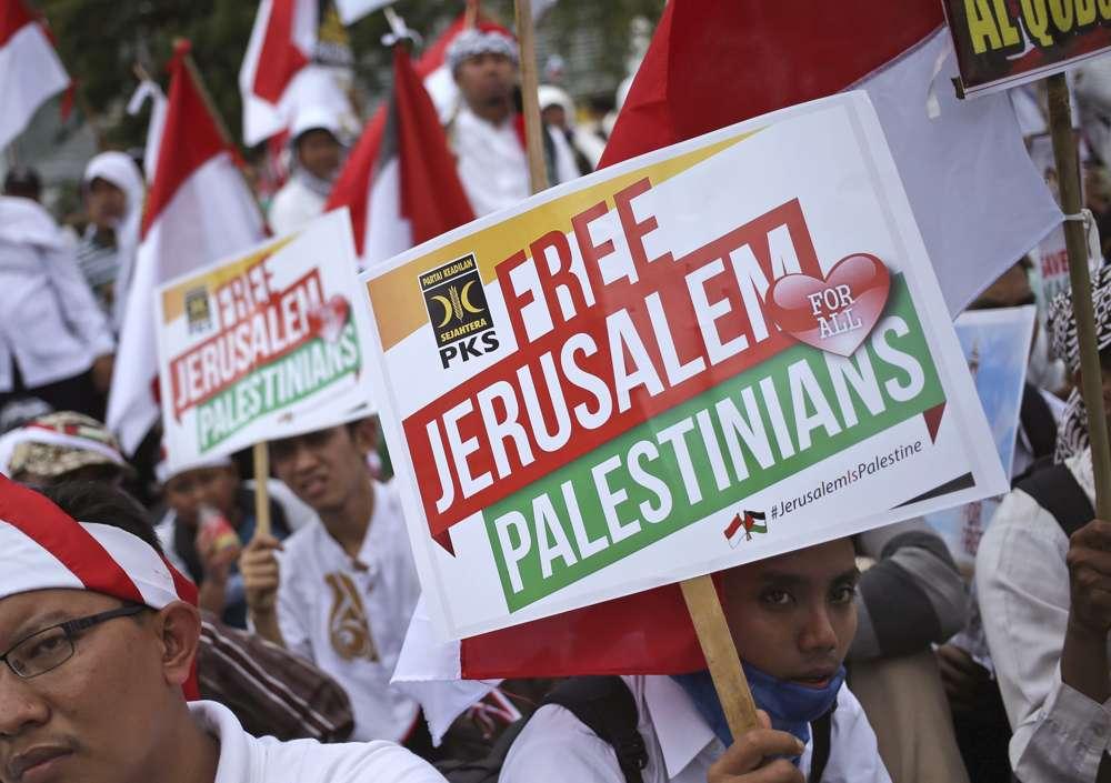 Hombres musulmanes sostienen carteles durante una manifestación frente a la embajada de Estados Unidos en Yakarta, Indonesia, en contra de la decisión del presidente estadounidense Donald Trump de reconocer a Jerusalém como la capital de Israel, 10 de diciembre de 2017. (AP Photo / Dita Alangkara)
