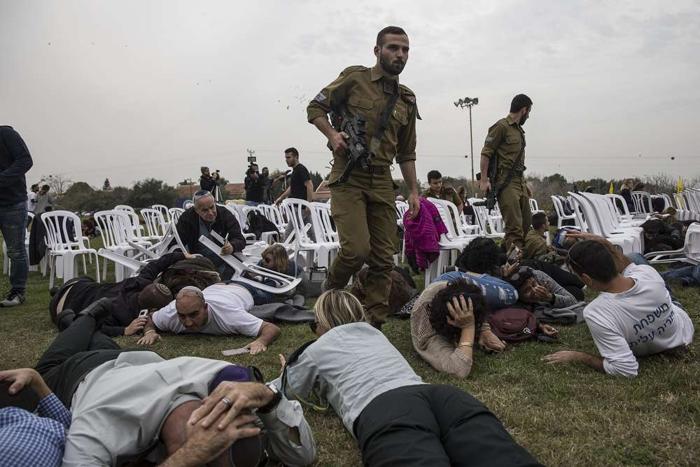 Israelíes se cubre durante una alerta de proyectil entrante en el Kibutz Kfar Aza cerca de la frontera entre Israel y Gaza, el viernes 29 de diciembre de 2017. Los israelíes se habían reunido allí para conmemorar el cumpleaños de Oron Shaul, quien fue asesinado durante la última guerra en Gaza; Hamas retiene sus restos. (AP Photo / Tsafrir Abayov)