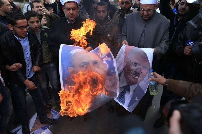 Los musulmanes queman fotos del presidente de EE.UU. Donald Trump y del primer ministro Benjamin Netanyahu en la ciudad de Gaza el 7 de diciembre de 2017. (AFP Photo / Mohammed Abed)