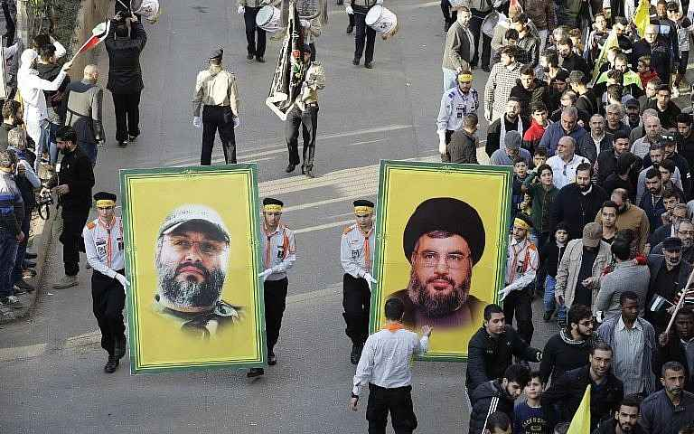 Los partidarios del grupo terrorista Hezbollah del Líbano sostienen retratos de su líder Hassan Nasrallah (R) y su ex jefe militar Imad Mughniyeh durante una protesta en Beirut el 11 de diciembre de 2017. (AFP Photo / Joseph Eid)