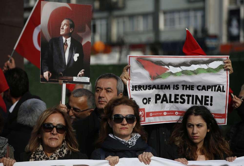 Manifestantes con banderas turcas y de la Autoridad Palestina y una pancarta de Mustafa Kemal Ataturk, el fundador de la Turquía moderna, entonan consignas antiestadounidenses durante una manifestación en Estambul, el sábado 9 de diciembre de 2017, contra la decisión del presidente estadounidense Donald Trump de reconocer Jerusalém en el capital de Israel. (AP Photo / Lefteris Pitarakis)