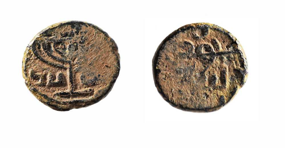 """Moneda omeya (después de la reforma) con un modelo de menorah de siete brazos. Hecha de bronce. Estas monedas probablemente fueron acuñadas en Jerusalém alrededor del siglo VIII EC. En un lado de la moneda hay una menorah de siete brazos con una inscripción en árabe: """"No hay más D'os que Alá"""". En el otro lado de la moneda hay una inscripción árabe, """"Muhammad, el mensajero de D'os"""", y arriba está el símbolo de la media luna musulmana. (Obsequio de la Colección Sofer de Abraham Sofer y Marianne Schweer, Palo Alto, Museo de Amigos Americanos de Israel, Jerusalém, Israel. © Museo de Israel, Jerusalén; Vladimir Nikhin)"""