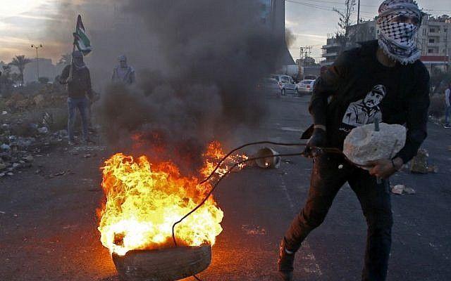 Un musulmán saca una llanta encendida durante una ola de ataques a las fuerzas de seguridad israelíes cerca de un puesto de control israelí en la ciudad de Ramallah el 9 de diciembre de 2017, luego del reconocimiento del presidente de los Estados Unidos a Jerusalén como la capital de Israel. (AFP / Abbas Momani)