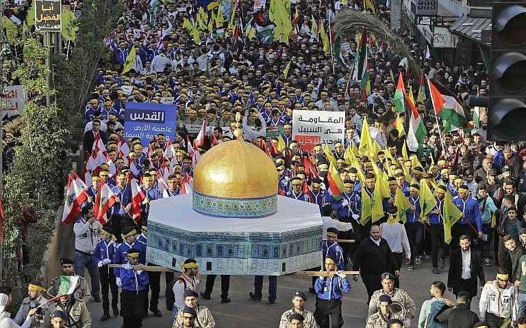 Partidarios del grupo terrorista Hezbollah de Líbano marchan con un modelo de la Cúpula de la Roca y agitan banderas libanesas, de la Autoridad Palestina y de Hezbolá durante una protesta en Beirut el 11 de diciembre de 2017. (AFP Photo / Joseph Eid)
