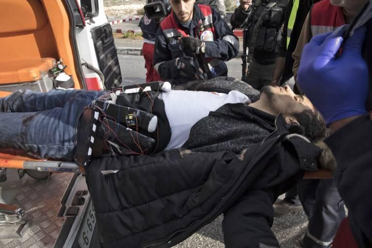 Terrorista musulmán Muhammed Aqal, que llevaba un presunto chaleco suicida, es llevado a una ambulancia después de apuñalar a un soldado y luego recibió un disparo en la ciudad de al-Bireh de Cisjordania el 15 de diciembre de 2017. (Oren Ziv / AFP)