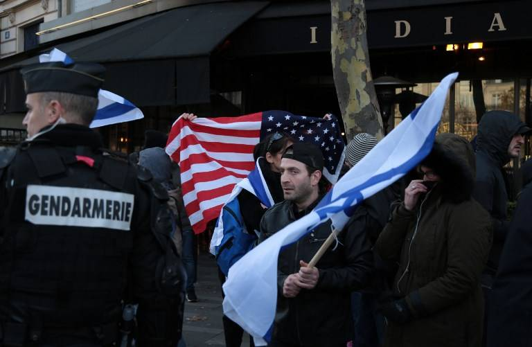 Un gendarme observa mientras un hombre ondea una bandera israelí y otro agita una bandera estadounidense mientras observa a los manifestantes que participan en una protesta anti-Israel en París el 9 de diciembre de 2017, contra el reconocimiento del presidente estadounidense Donald Trump de Jerusalém como la capital de Israel . (AFP / Zakaria Abdelkafi)