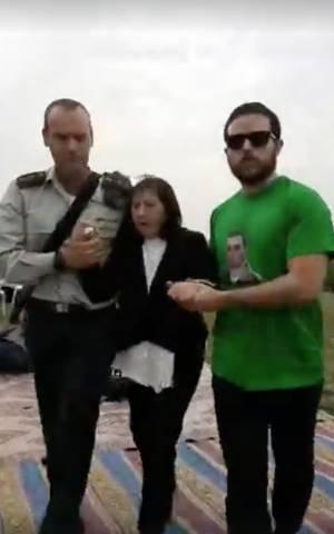 Zehava Shaul, madre de Oron cuyos restos están en poder del grupo terrorista Hamas en Gaza, es apartada de una ceremonia en su honor después del lanzamiento de cohetes en Israel desde el enclave costero el 29 de diciembre de 2017. (Captura de pantalla)
