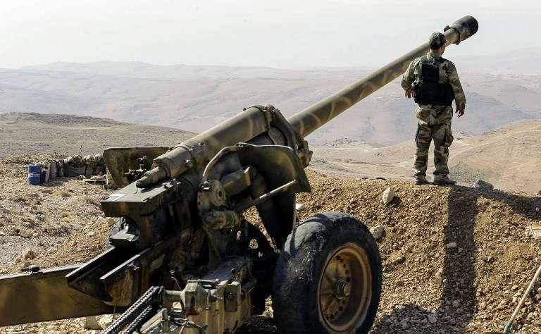 Una visita guiada por el grupo terrorista chiita libanés Hezbollah muestra a uno de los combatientes del grupo junto a una artillería en una zona montañosa alrededor de la ciudad Siria de Flita, cerca de la frontera con Líbano, el 2 de agosto de 2017. (AFP PHOTO / LOUAI BESHARA)
