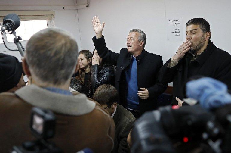 Bassem Tamimi (C), padre de la atacante árabe de 16 años, Ahed Tamimi, saluda a su hija durante una audiencia en el tribunal militar israelí en la prisión militar de Ofer el 15 de enero de 2018. (Thomas Coex / AFP)