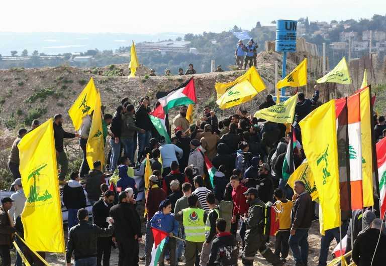 Soldados israelíes (arriba L) y fuerzas de paz de la ONU (arriba R) observan a los partidarios libaneses del movimiento chiita de Hezbollah presencian una manifestación contra la decisión del presidente estadounidense de reconocer a Jerusalem como la capital de Israel el 28 de enero de 2018 en la aldea libanesa del sur de Alma al-Shaab, en la frontera con Israel. (AFP / Mahmoud Zayyat)
