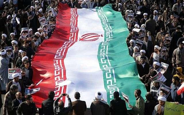 Los manifestantes progubernamentales agitan su bandera nacional durante una marcha en la ciudad de Qom, en Irán, a unos 130 kilómetros al sur de Teherán, el 3 de enero de 2018. (AFP PHOTO / Mohammad ALI MARIZAD)