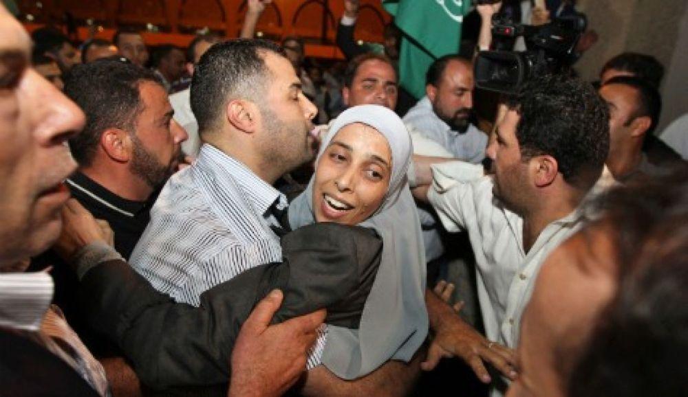 El jordano Ahlam Tamimi, recién liberado de una prisión israelí, fue abrazado por un pariente a su llegada al aeropuerto internacional Queen Alia en Amman el 18 de octubre de 2011. Reuters