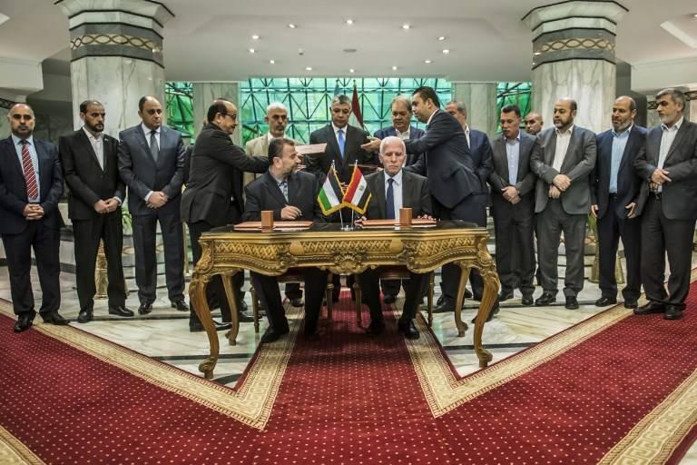 El nuevo vicepresidente de Hamas, Salah al-Arouri (sentado L) y Azzam al-Ahmad (sentado R) firman un acuerdo de reconciliación en El Cairo el 12 de octubre de 2017, mientras los dos movimientos rivales palestinos trabajan para terminar su separación de una década después de negociaciones supervisado por Egipto. (AFP Photo / Khaled Desouki)