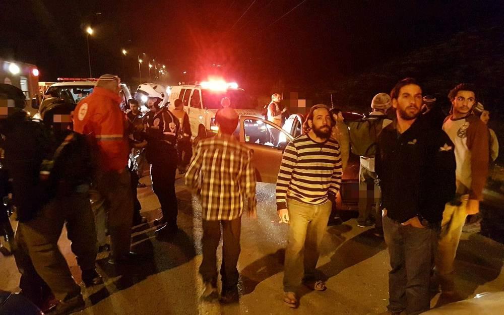 La gente se reúne en la escena de un ataque terrorista cerca de Gilad Farm Junction en Judea y Samaria el 9 de enero de 2018. (Magen David Adom)