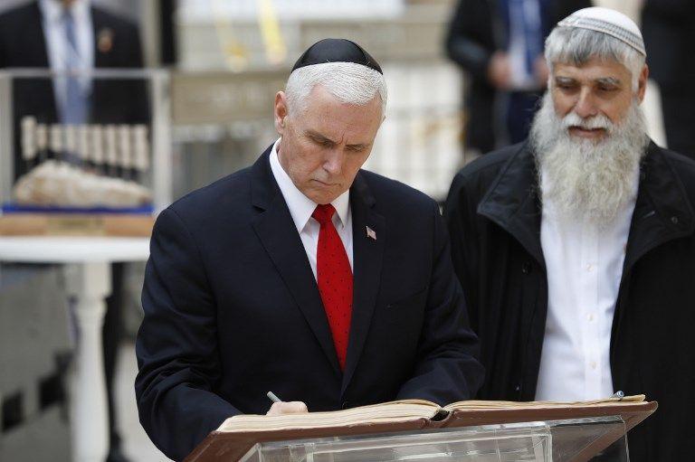El vicepresidente de EE.UU. Mike Pence (izq.) Firma el libro de visitas durante una visita al Muro Occidental de Jerusalem el 23 de enero de 2018. (AFP PHOTO / Thomas COEX)