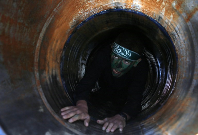 Un árabe se arrastra en un túnel durante una ceremonia de graduación de un campo de entrenamiento dirigido por el movimiento terrorista Hamas el 29 de enero de 2015, en Khan Yunis, en el sur de la Franja de Gaza. (Foto AFP / Said Khatib)