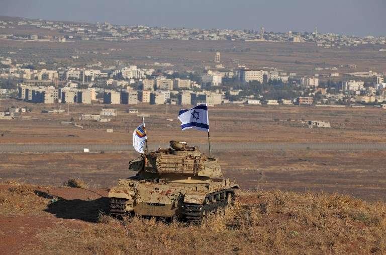 Una bandera Israelí flamea sobre los restos de un tanque en una colina en los Altos del Golán con vistas a la frontera con Siria el 18 de octubre de 2017. (AFP Photo / Jalaa Marey)