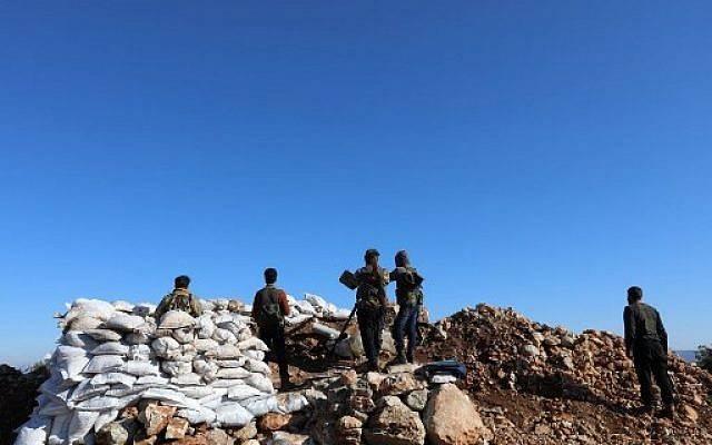 Una fotografía tomada el 20 de enero de 2018, desde la aldea de Qilah en la provincia de Idlib, muestra a combatientes rebeldes sirios de pie cerca del enclave kurdo de Afrin. (AFP PHOTO / OMAR HAJ KADOUR)