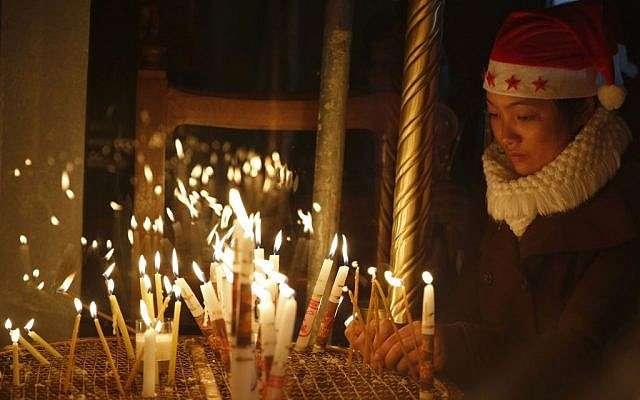 Uno de los cristianos ortodoxos enciende una vela en la Iglesia de la Natividad, construida sobre el sitio donde los cristianos creen que nació Jesus, en la víspera de Navidad, en la ciudad de Belén, el 24 de diciembre de 2016 (AP Photo / Majdi Mohammed)