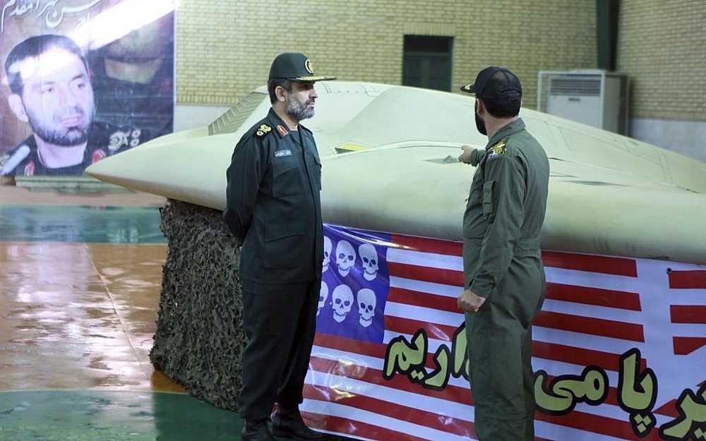 Jefe de la división aeroespacial de la Guardia Revolucionaria de Irán, Amir Ali Hajizadeh (izquierda), cerca del avión no tripulado Sentinel estadounidense RQ-170 capturado en abril de 2012. (Crédito de la foto: AP / Sepahnews)