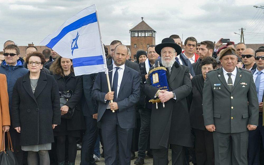 El ministro de Educación Naftali Bennett (2º-L), el rabino Meir Lau (2º-R) y el jefe de personal de las FDI Gadi Eisenkot (R) participan en la Marcha de los Vivos en el campamento de Auschwitz-Birkenau en Polonia el 24 de abril de 2017. (Yossi Zeliger / Flash 90)
