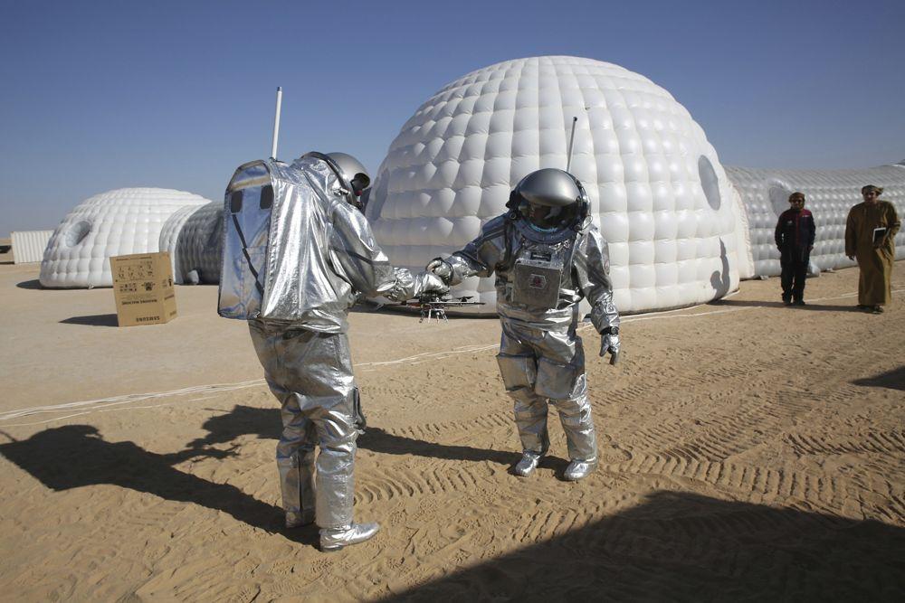 El astronauta analógico João Lousada, centro, le entrega a su colega Kartik Kumar un dron mientras dos hombres omaníes miran frente al campamento base de simulación de Marte en el desierto de Dhofar en Omán, el 7 de febrero de 2018. (AP Photo / Sam McNeil)
