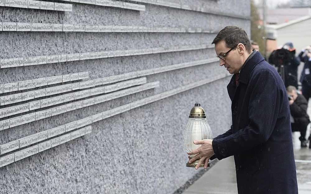 El primer ministro polaco Mateusz Morawiecki coloca una vela en una pared conmemorativa con los nombres de algunos de los polacos que salvaron judíos durante el Holocausto, en el Museo de la Familia Ulma de los polacos que salvaron judíos durante la Segunda Guerra Mundial, en Markowa, Polonia, 2 de febrero de 2018. (AP / Alik Keplicz)