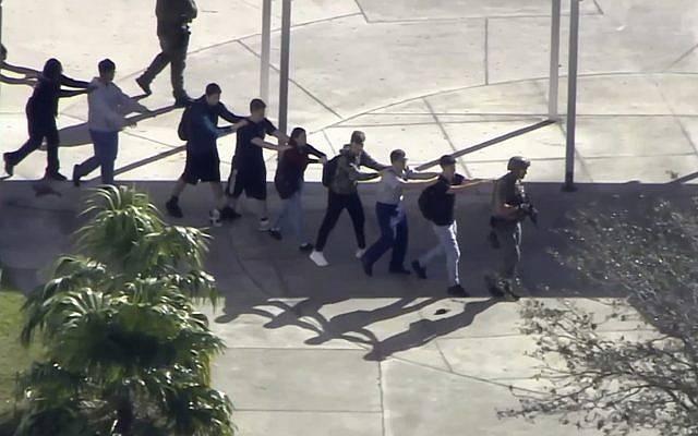 Los estudiantes de la Marjory Stoneman Douglas High School en Parkland, Fla., Evacuan la escuela luego de un tiroteo el 14 de febrero de 2018. (WPLG-TV vía AP)