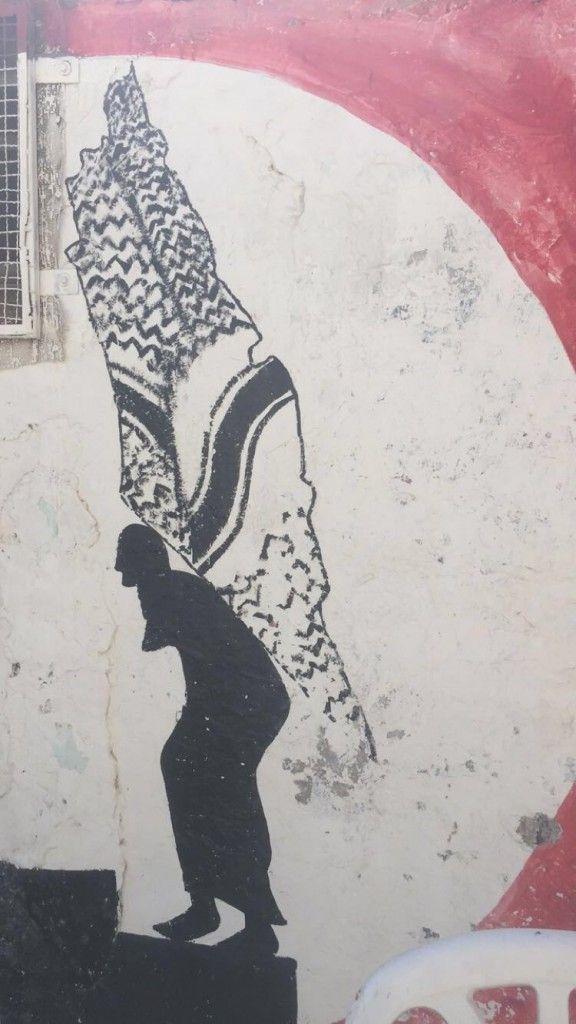 Graffiti de un hombre con un mapa de Israel con estampado de keffiyeh en la espalda. Ramallah. (Lilia Gaufberg)