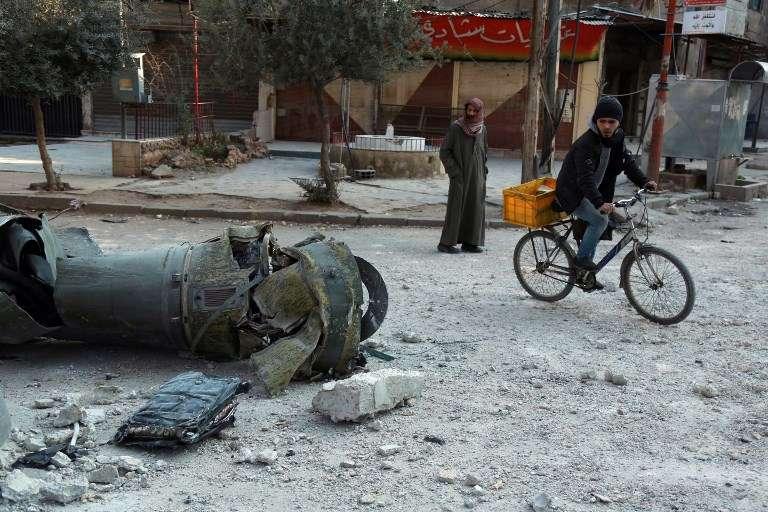 Hombres sirios caminan junto a los restos de un cohete en la ciudad de Douma, en la sitiada región oriental de Ghouta, en las afueras de la capital, Damasco, tras los ataques aéreos de las fuerzas del régimen en la zona el 23 de febrero de 2018. (AFP PHOTO / HAMZA AL-AJWEH)
