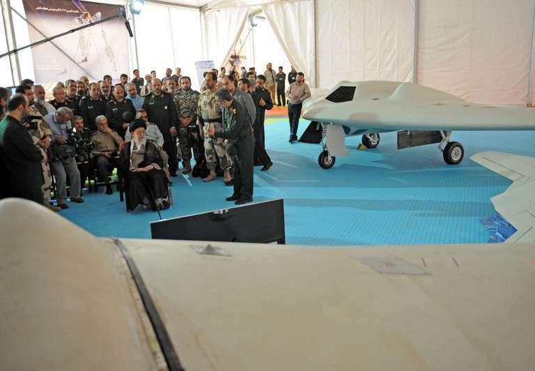 Una foto de la oficina de Khamenei , el Líder Supremo de Irán el 11 de mayo de 2014 lo muestra (CL) sentado al lado de un dron RQ-170 y su copia local en la exhibición de la Fuerza Aérea Espacial de la Guardia Revolucionaria Islámica en Teherán.(AFP / HO / sitio web del líder iraní)