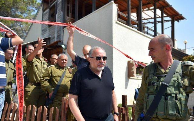El ministro de defensa Avigdor Liberman (centro) camina ante el jefe del Estado Mayor de las FDI Gadi Eisenkot (cuarta izquierda) mientras visitan el sitio de un ataque terrorista en el poblado judío de Halamish, 22 de julio de 2017 (Ariel Hermoni / Ministerio de Defensa vía Flash 90)