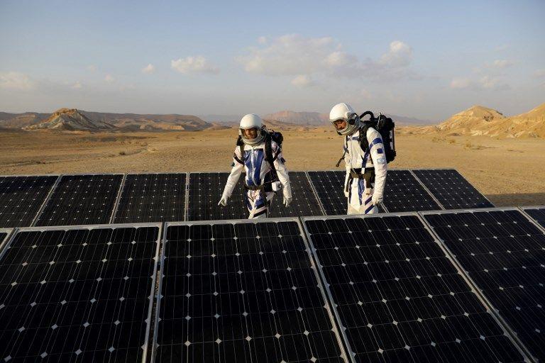 Los astronautas análogos israelíes caminan pat paneles solares cuando comienzan su misión en el Proyecto D-MARS el 18 de febrero de 2018. (AFP / MENAHEM KAHANA)