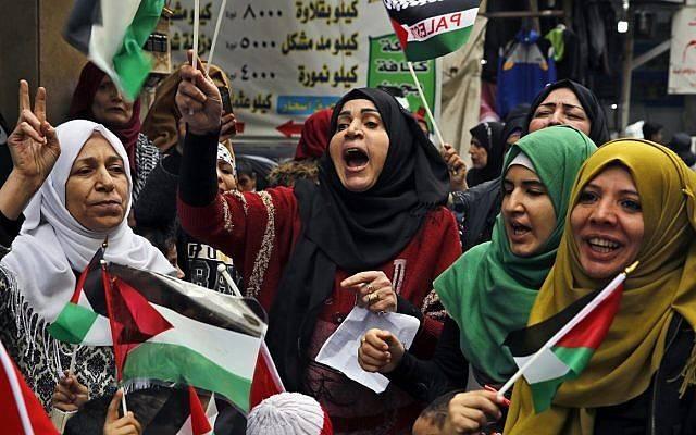 Mujeres árabes gritan consignas mientras sostienen banderas palestinas durante una sentada en el campamento de refugiados palestinos de Bourj al-Barajneh, en Beirut, Líbano, el 6 de diciembre de 2017. (AP Photo / Bilal Hussein)