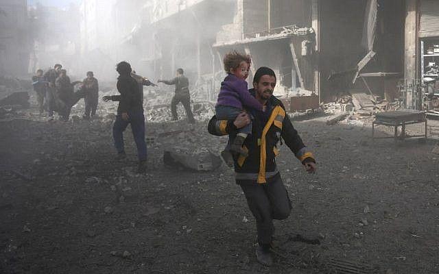 Un hombre sirio porta a un niño herido en un bombardeo del gobierno en la ciudad de Hamouria, en la sitiada región de Ghouta, en las afueras de la capital, Damasco, el 19 de febrero de 2018. (AFP PHOTO / ABDULMONAM EASSA)