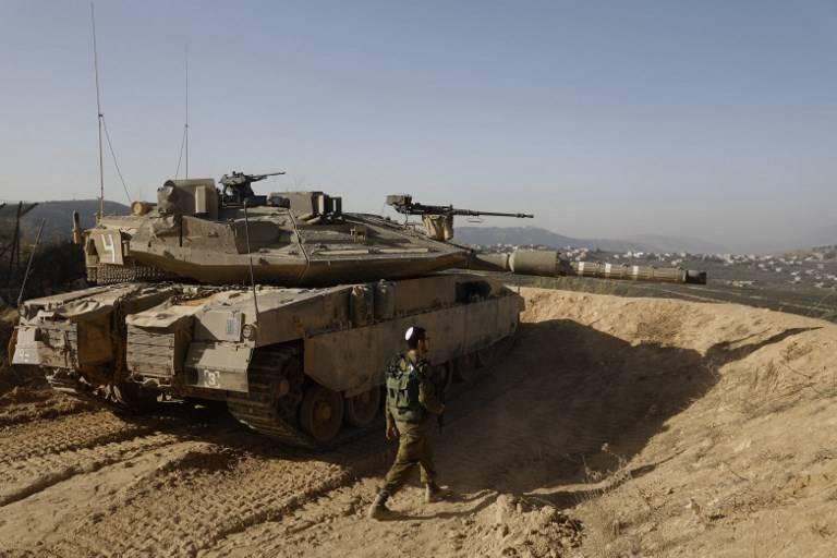Una foto tomada el 16 de noviembre de 2017 muestra a un soldado israelí caminando al lado de un tanque en una posición del ejército con vista al sur del Líbano en la ciudad de Metula, al norte de Israel, a lo largo de la frontera de Israel con Líbano. (AFP PHOTO / MENAHEM KAHANA)