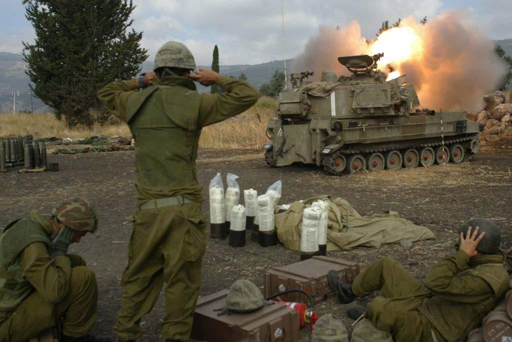 Soldados israelíes se cubren los oídos mientras disparan proyectiles de artillería en el sur del Líbano desde las afueras de Kiryat Shmona, en el norte de Israel, durante la Segunda Guerra del Líbano, el 22 de julio de 2006. (Pierre Terdjman / Flash 90)