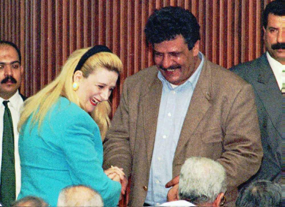 Suha Arafat, esposa del líder de la OLP Yasser Arafat, saluda al cerebro del secuestro del Achille Lauro, Abul Abbas, antes del inicio de la primera sesión del Consejo Nacional Palestino en la ciudad de Gaza, el 22 de abril de 1996. (AP / Adel Hana)