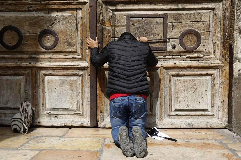 Un peregrino reza frente a la puerta cerrada de la iglesia del Santo Sepulcro en la Ciudad Vieja de Jerusalem el 25 de febrero de 2018. (AFP PHOTO / GALI TIBBON)