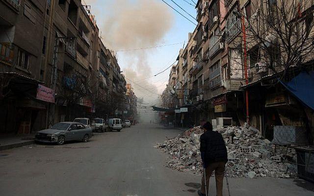 Un sirio con muletas camina por una calle mientras el humo se expande en la ciudad rebelde de Douma, en la sitiada región oriental de Ghouta, en las afueras de la capital, Damasco, tras los ataques aéreos de las fuerzas del régimen en la zona, el 23 de febrero de 2018. (AFP / HAMZA AL-AJWEH)